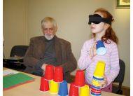 Dziewczynka bezbłędnie rozpoznaje kolory kubków, mimo że oczy przesłania jej opaska.