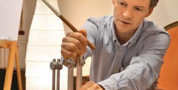 Terapeuta Mariusz Jarymowicz w czasie przygotowań do zabiegu z użyciem kamertonów